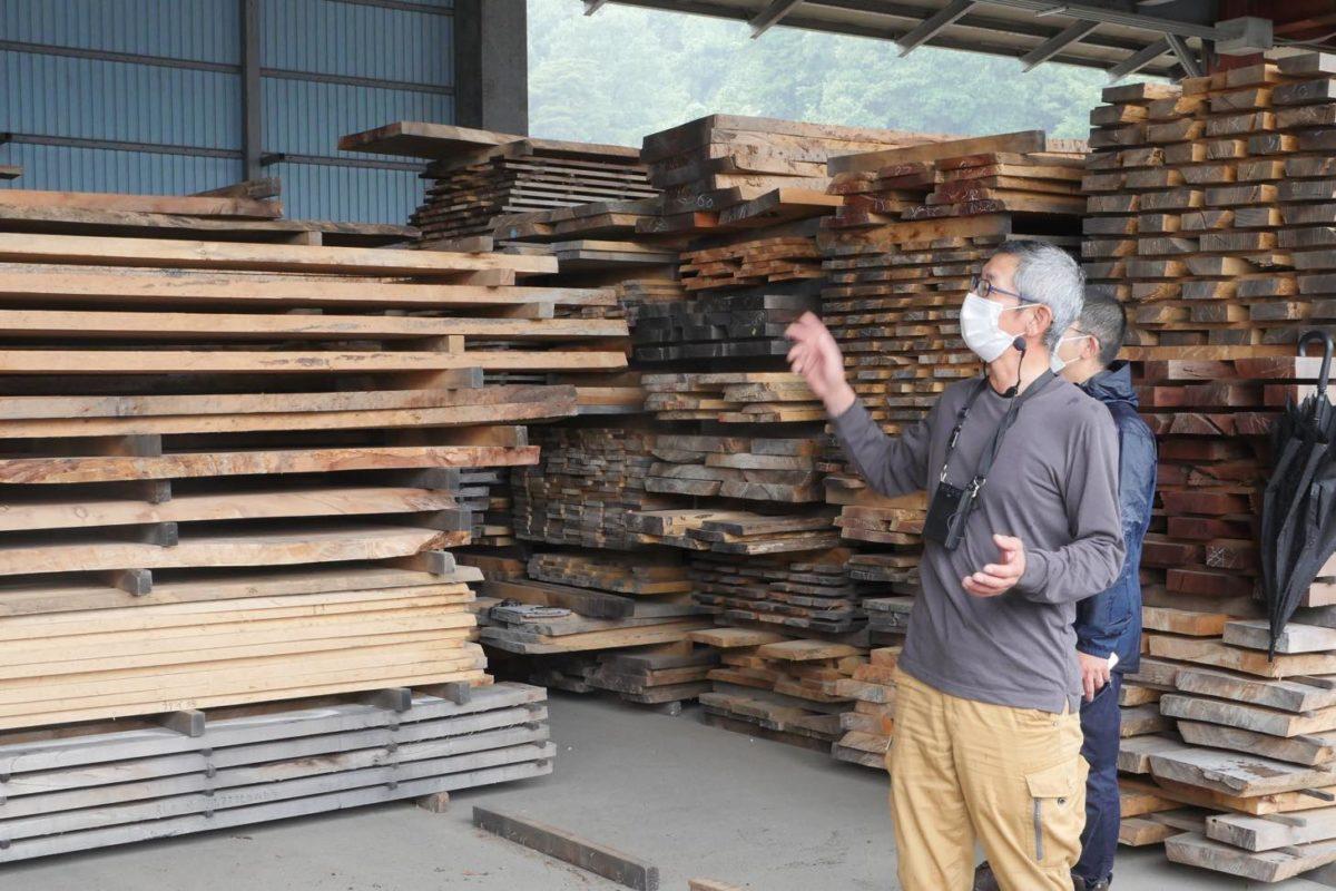 製材された板の前で小径木活用などについて説明する西野さん